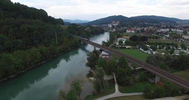 sorvolando un fiume fino a un ponte dove passa un treno video