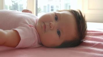 Baby, das auf rosa Decke liegt, schoss in Zeitlupe