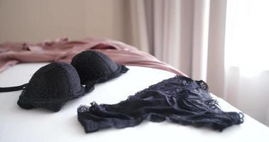 Cordão e sutiã pendurados na cama. close up shot video