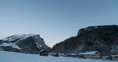 Laps de temps du lever du soleil sur un village alpin révélant les sommets des montagnes rocheuses