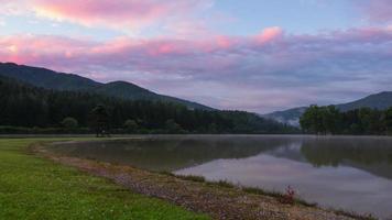 alba nebbiosa nel lago della foresta di montagna. lasso di tempo uhd video