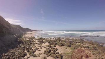 vista aérea de praia rochosa, penhasco e ondas quebrando na praia em dia de sol - praia de santa cruz, torres vedras, portugal