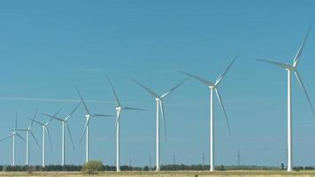 Molinos de viento girando visto en perspectiva sobre un cielo azul con un pequeño edificio y una línea de árboles video