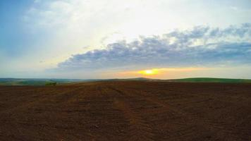 Ploughed Land and Clouds. Panorama. Time Lapse UHD