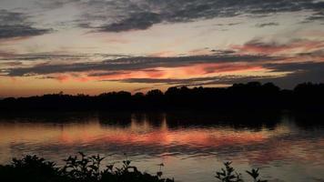 rio tranquilo fluindo em frente ao pôr do sol laranja