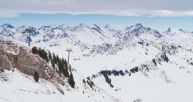 Zeitraffer von Skiliften mit schneebedeckten Alpen im Hintergrund
