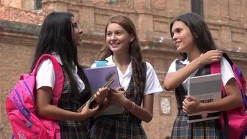 Studentinnen mit Lehrbüchern und Rucksäcken
