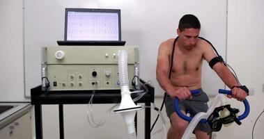 homem apto fazendo um teste de estresse em bicicleta ergométrica video