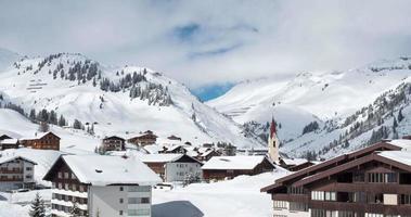 lapso de tempo de nuvens movendo-se sobre uma idílica aldeia na montanha na Áustria video