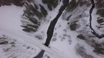 vista aérea acima da ponte coberta de neve e do curso de água congelado no inverno - harads, município de boden, norrbotten, suécia video