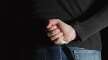 Gefahr Mann mit einem Messer hinter dem Rücken kommt in den Rahmen und geht weiter