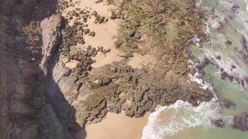 Vista aérea superior de las olas de agua blanca rompiendo en las rocas - Praia de Santa Cruz, Torres Vedras, Portugal