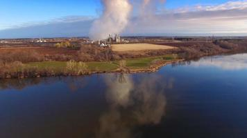 Rural landscape with factory or power plant overshadowing farms video