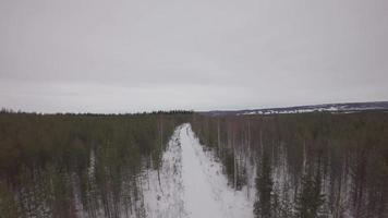 Vue aérienne au-dessus d'une route enneigée entre les pins - harads, municipalité de Boden, Norrbotten, Suède