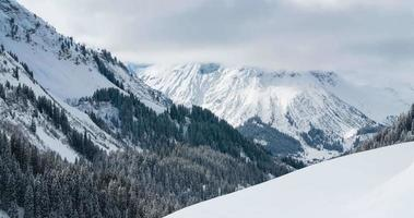 lapso de tempo de nuvens sobre um vale alpino com topos de montanhas cobertas de neve video