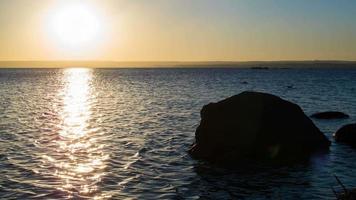 puesta de sol sobre el río sobre un fondo de piedras. lapso de tiempo video