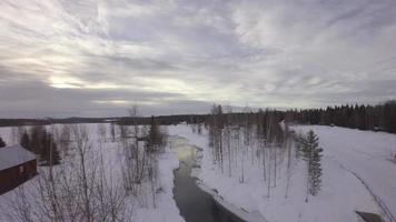 vista aérea de um curso de água com águas claras e lago congelado perto de uma vila de chalés - harads, município de boden, norrbotten, suécia video