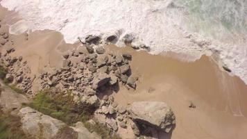 Vista aerea dall'alto delle onde di acqua bianca che si infrangono sulle rocce - praia de santa cruz, torres vedras, portogallo