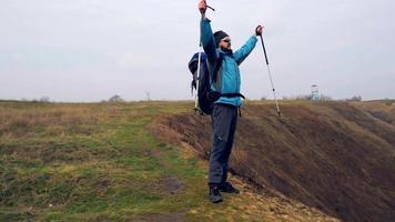 Mann Tourist in einer blauen Jacke mit einem Rucksack genießt sein Klettern video
