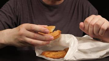 Mann, der Donuts nimmt und Donuts isst
