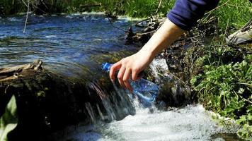 jeune randonneur recueille de l'eau dans une bouteille