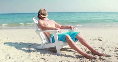 uomo che si distende sulla sedia a sdraio in spiaggia