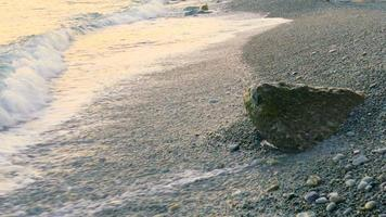Meereswellen am einsamen Strand bei Sonnenuntergang