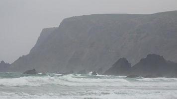 scogliere costiere e onde dell'oceano durante la nebbia