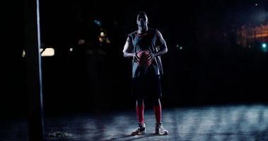 männlicher Basketballspieler, der am Abend Ball auf dem Platz hält