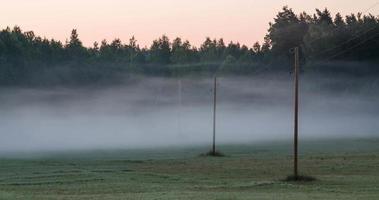 Laps de temps du brouillard du matin circulant entre les lignes électriques