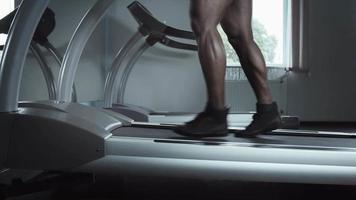 Laufende männliche Beine auf dem Laufband erhöhen die Neigung