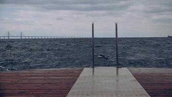 ondas espirrando no cais de madeira do oceano em dia de tempestade