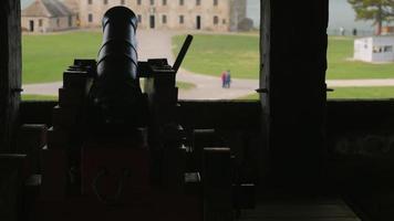 Viejo cañón en Fort Niagara. detrás de ella un gran edificio fuerte
