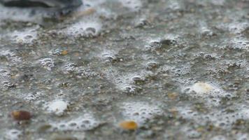 schäumende Wellen auf den Kieselsteinen, Nahaufnahme