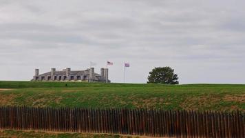 edificio principal del fuerte del niágara. a través de brevenchasty empalizada techo visible y tres banderas
