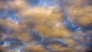 geschwollene Zuckerwattewolken, die sich im Zeitraffer des Sonnenuntergangs durch den Himmel bewegen
