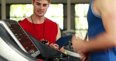 Male trainer writing about treadmill performance
