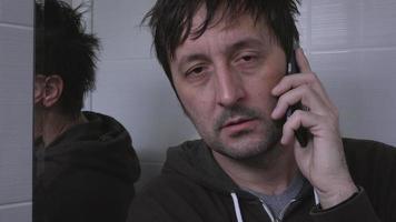 Erwachsener Mann mit privatem Mobiltelefongespräch im Badezimmer