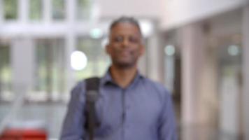Maestro negro de mediana edad caminando hacia el foco en un vestíbulo