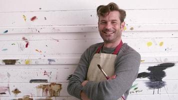 Artista masculino apoyado contra la pared cubierta de pintura rodada en r3d