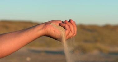 sable glissant entre les doigts de la main masculine au ralenti
