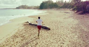 4K Young Fit Male Running on Beach. Aerial Fly By. Outdoor Healthy Lifestyle.