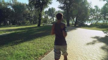 um jovem com fones de ouvido e roupas esportivas corre um dia de verão, árvores verdes