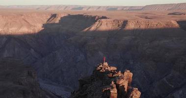 Panoramique 4k de touristes masculins debout sur le pinacle de la roche en tenant compte du canyon de la rivière Fish