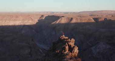 4K Panning shot of Male tourist standing on rock pinnacle taking in the view of Fish River Canyon