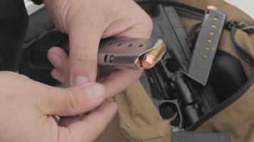 Hombre cargando balas en un cargador de pistola
