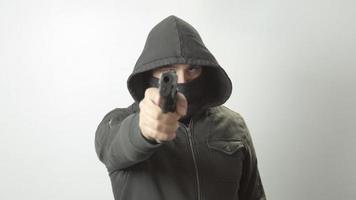 Hooded Masked Man Points Handgun at Camera