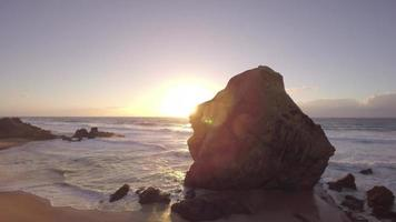 vista aérea de uma rocha de pedra na praia à beira-mar ao pôr do sol, flare - praia de santa cruz, torres vedras, portugal