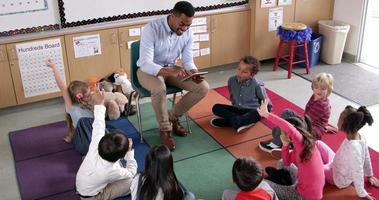 l'enseignant présente un livre d'histoires aux jeunes élèves, vue élevée