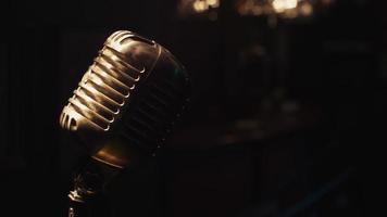 il microfono da concerto resta sul palco sotto i riflettori. scrubwoman bugia sul bancone del bar